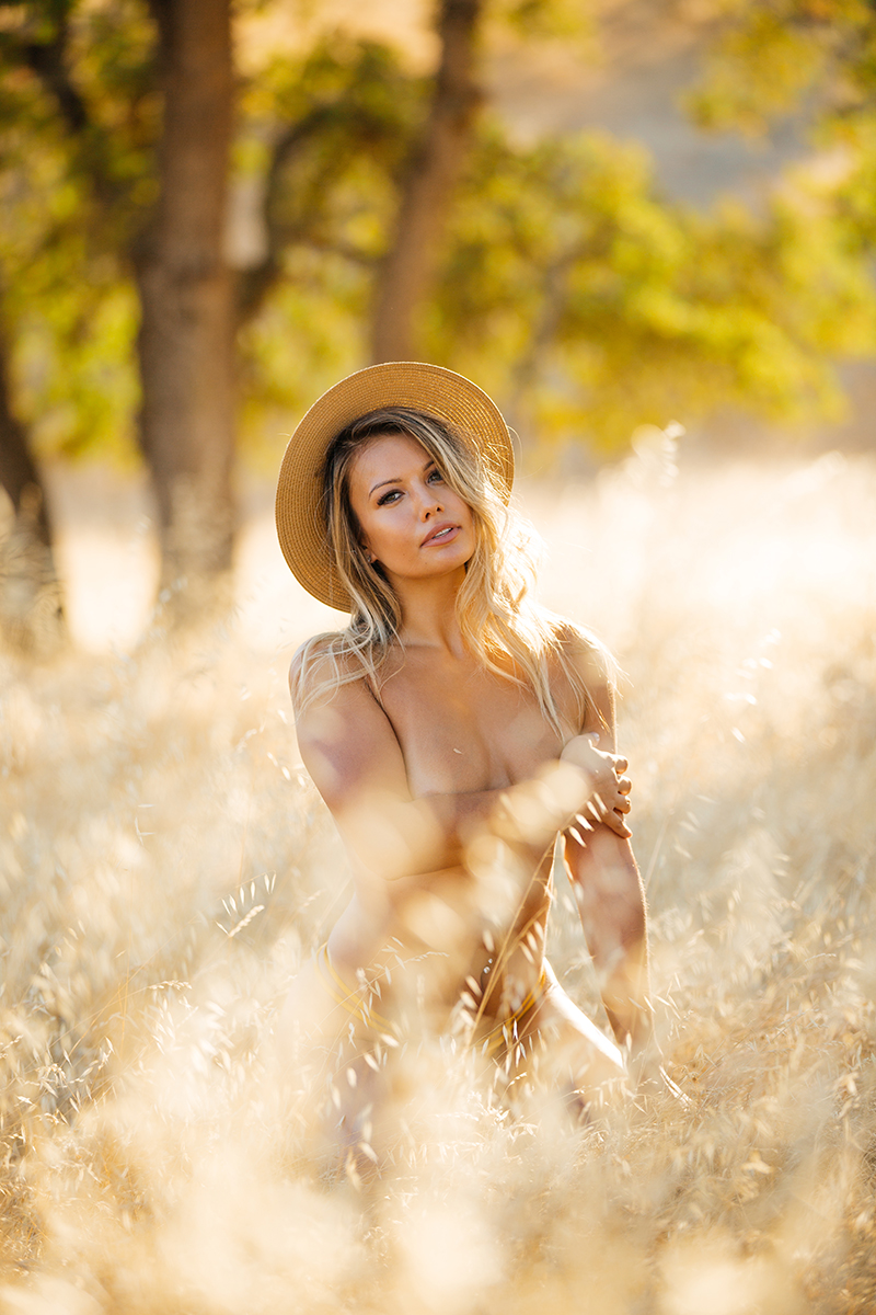 A young beautiful blonde woman posing topless in a field with trees as the sun sets with a straw hat covering her breasts with her hand on a trail near Rancho Murieta for a Deer Creek Hills boudoir photography session