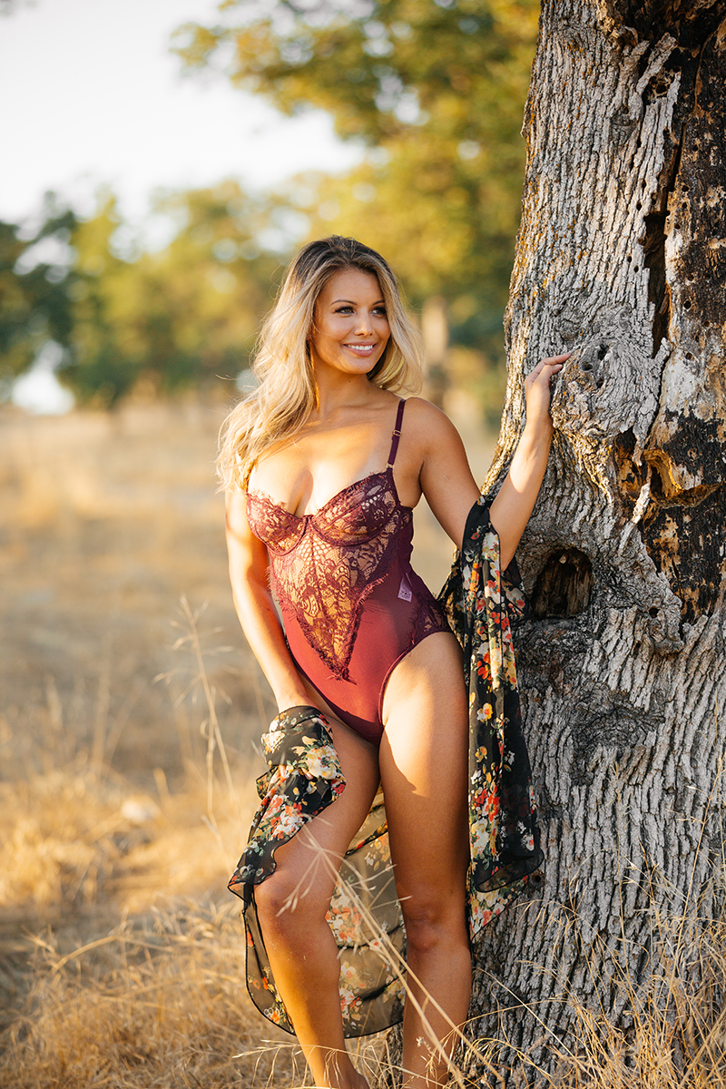 A young beautiful blonde woman posing against a tree in a field as the sun sets in red lingerie and a floral robe on a trail near Rancho Murieta for a Deer Creek Hills boudoir photography session