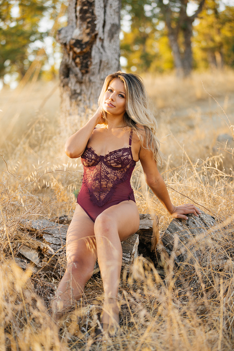 A young beautiful blonde woman sitting on a log in a field as the sun sets in red lingerie on a trail near Rancho Murieta for a Deer Creek Hills boudoir photography session