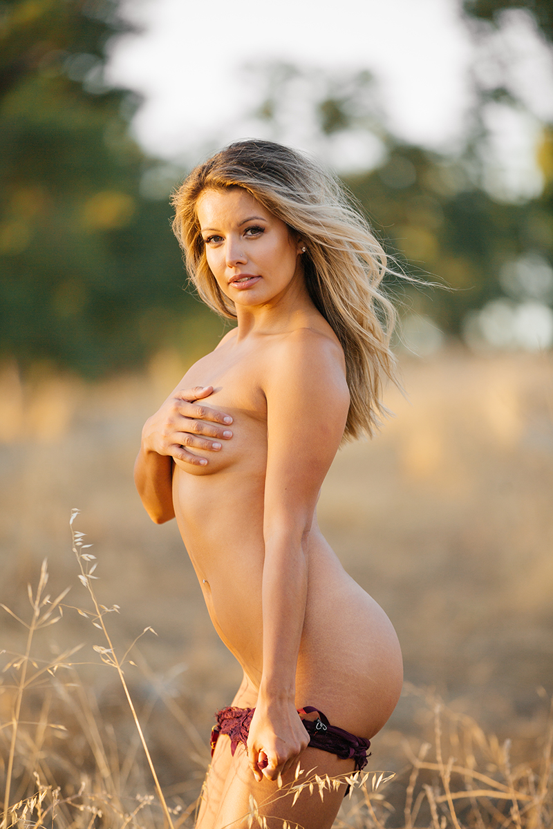 A young beautiful blonde woman poses nude in a field as the sun sets on a trail near Rancho Murieta for a Deer Creek Hills boudoir photography session