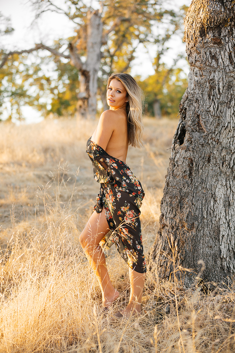 A young beautiful blonde woman poses nude in a field covering with a floral robe as the sun sets on a trail near Rancho Murieta for a Deer Creek Hills boudoir photography session