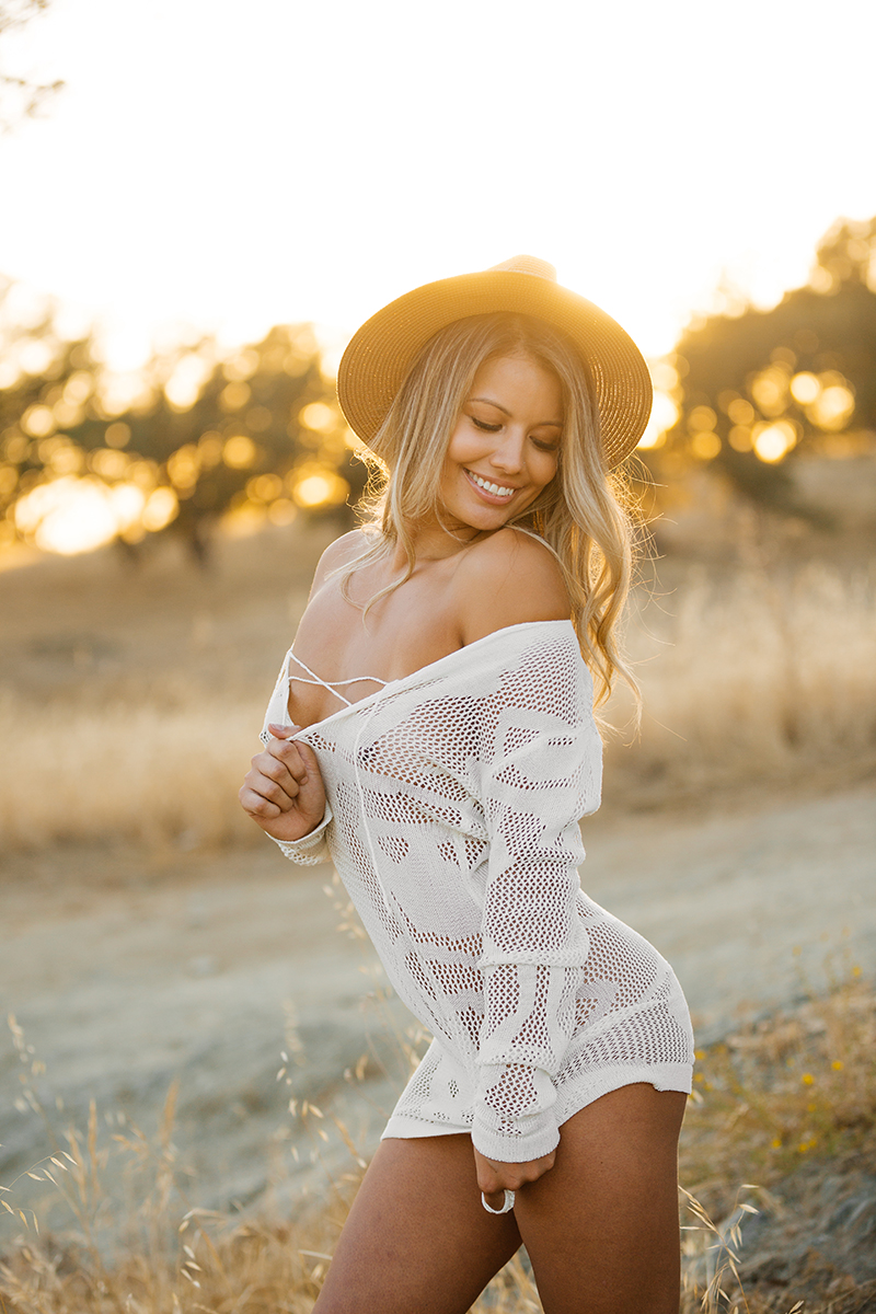 A young beautiful blonde woman poses in a field wearing a straw hat and a white lace dress as the sun sets on a trail near Rancho Murieta for a Deer Creek Hills boudoir photography session