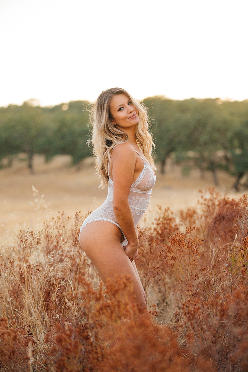 A young beautiful blonde woman poses in a field wearing white lingerie as the sun sets on a trail near Rancho Murieta for a Deer Creek Hills boudoir photography session