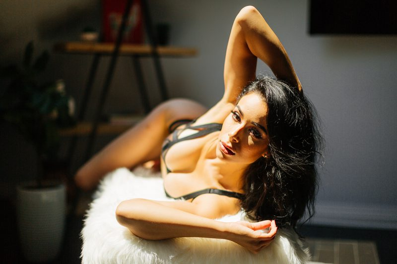 A beautiful brunette woman poses in a black bra and black underwear on a fuzzy bench in sunlight for a Denver loft boudoir photography session at an Airbnb in Colorado