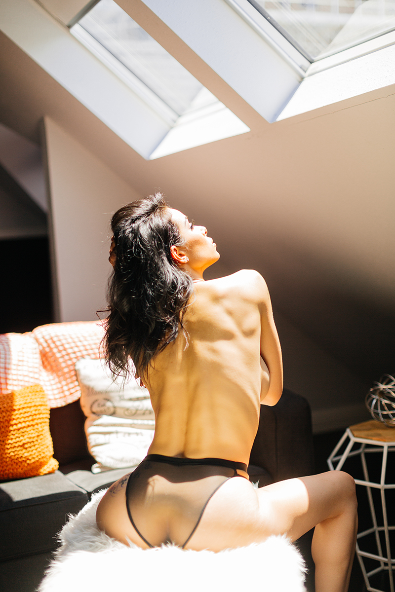 A beautiful brunette woman poses topless on a fuzzy bench in sunlight for a Denver loft boudoir photography session at an Airbnb in Colorado