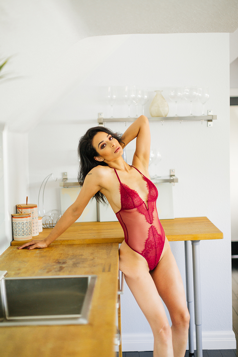 A beautiful brunette woman poses in red lingerie next to a wood counter in the kitchen for a Denver loft boudoir photography session at an Airbnb in Colorado