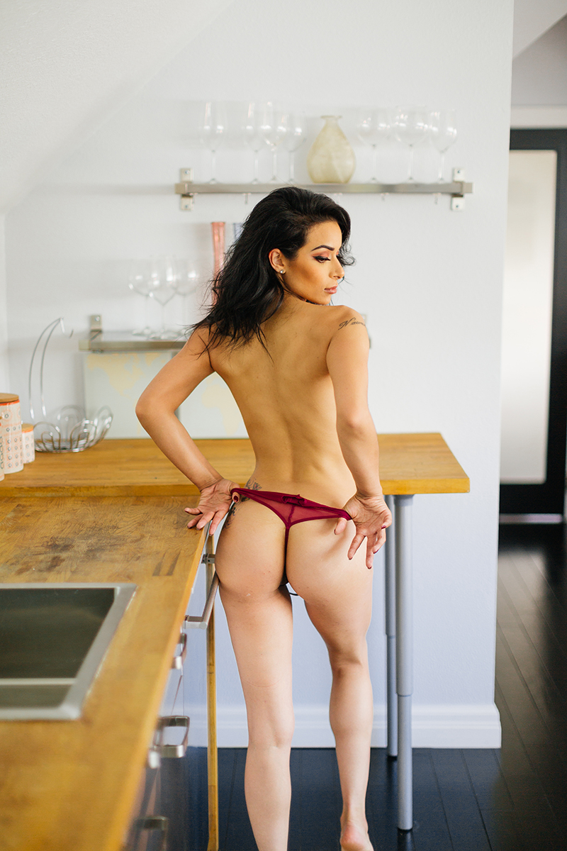 A beautiful brunette woman poses topless in red lingerie next to a wood counter in the kitchen for a Denver loft boudoir photography session at an Airbnb in Colorado