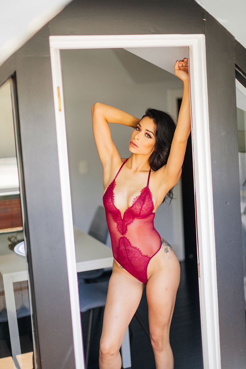 A beautiful brunette woman poses in red lingerie in a doorway for a Denver loft boudoir photography session at an Airbnb in Colorado