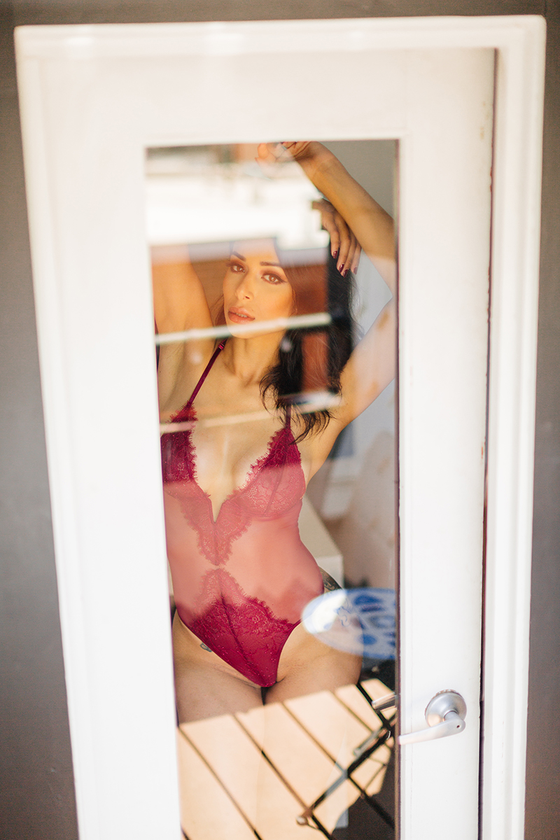 A beautiful brunette woman poses in red lingerie behind glass in a doorway for a Denver loft boudoir photography session at an Airbnb in Colorado