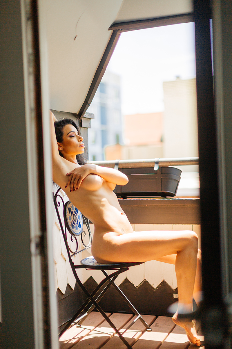 A beautiful brunette woman poses in nude on a patio for a Denver loft boudoir photography session at an Airbnb in Colorado