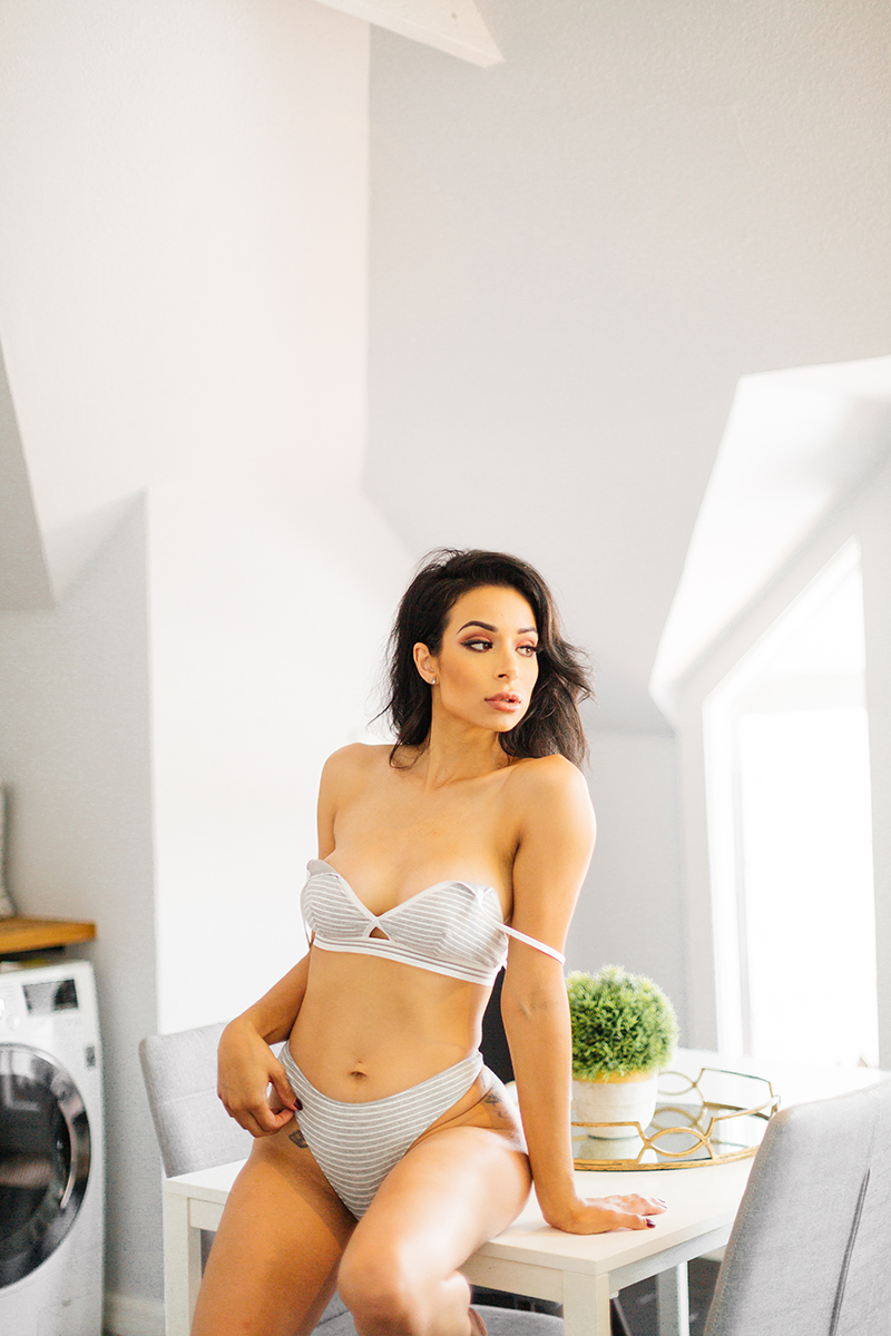 A beautiful brunette woman poses in gray Calvin Klein bra and underwear on a table for a Denver loft boudoir photography session at an Airbnb in Colorado