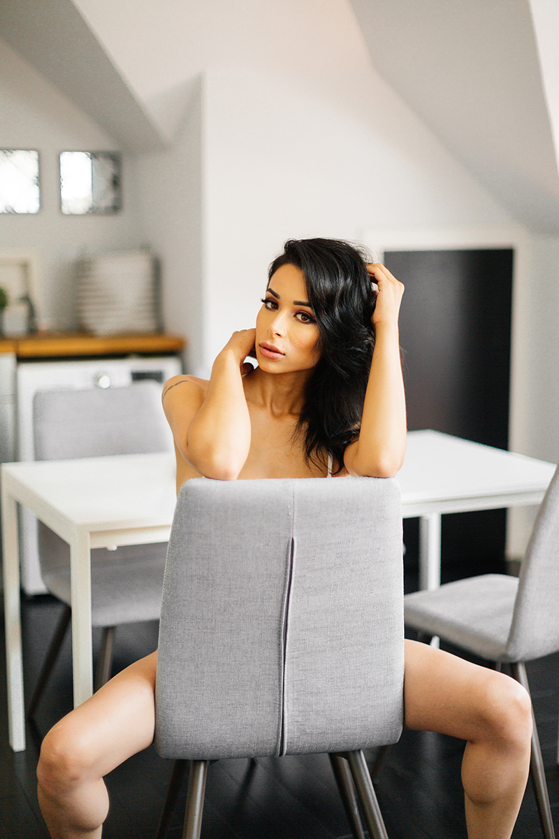A beautiful brunette woman poses topless sitting in a chair at a table for a Denver loft boudoir photography session at an Airbnb in Colorado