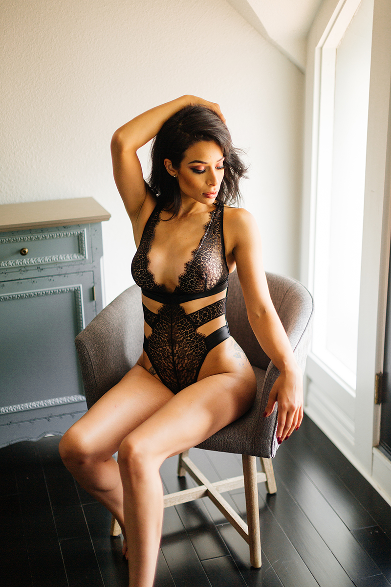A beautiful brunette woman poses in black lingerie in a chair for a Denver loft boudoir photography session at an Airbnb in Colorado