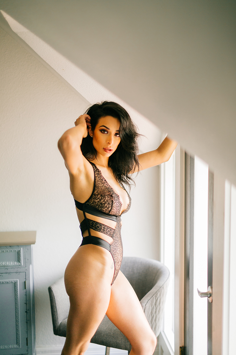 A beautiful brunette woman poses in black lingerie standing near a window for a Denver loft boudoir photography session at an Airbnb in Colorado
