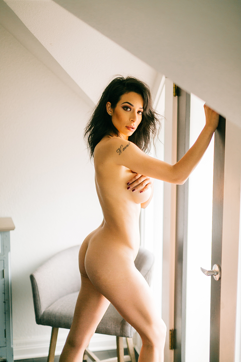 A beautiful brunette woman poses nude while standing near a window for a Denver loft boudoir photography session at an Airbnb in Colorado