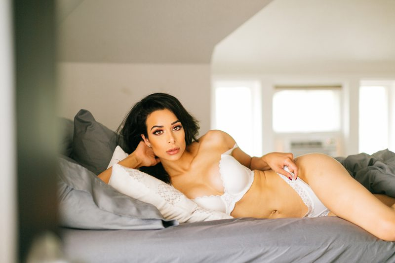 A beautiful brunette woman poses in white underwear and bra on a bed for a Denver loft boudoir photography session at an Airbnb in Colorado