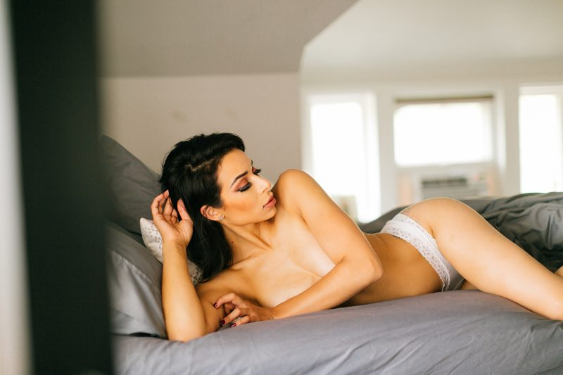 A beautiful brunette woman poses topless in white underwear on a bed for a Denver loft boudoir photography session at an Airbnb in Colorado