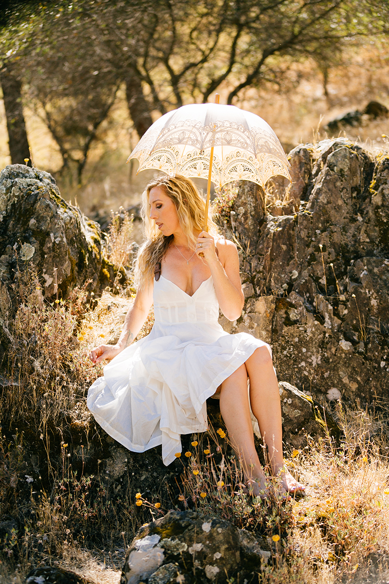 A beautiful blonde woman wearing a white dress with leather straps holding an umbrella while sitting on rocks on a hillside for an American River boudoir photography session near Auburn, California