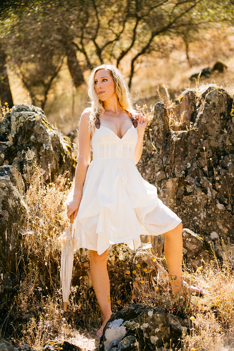 A beautiful blonde woman wearing a white dress with leather straps holding an umbrella while standing in front of rocks on a hillside for an American River boudoir photography session near Auburn, California