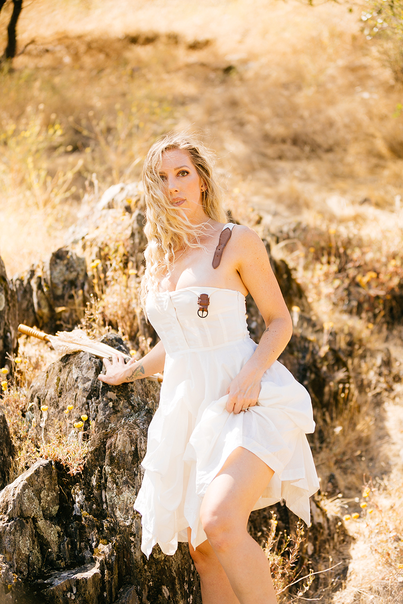 A beautiful blonde woman wearing a white dress with leather straps while standing in front of rocks on a hillside for an American River boudoir photography session near Auburn, California