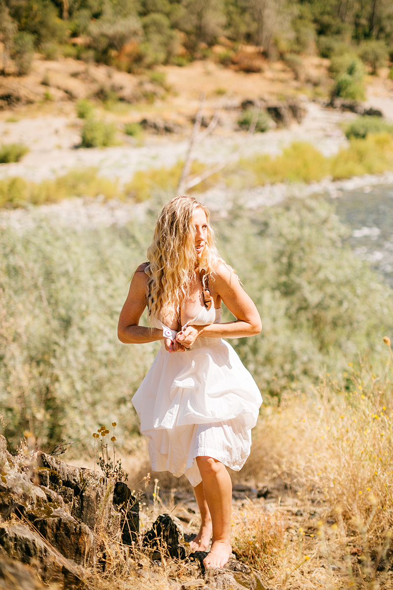 A beautiful blonde woman wearing a white dress with leather straps standing in front of the American River for an American River boudoir photography session near Auburn, California