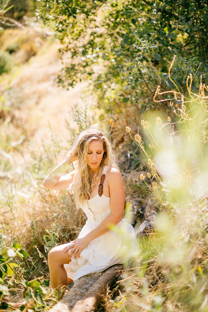 A beautiful blonde woman wearing a white dress with leather straps sitting in a field for an American River boudoir photography session near Auburn, California