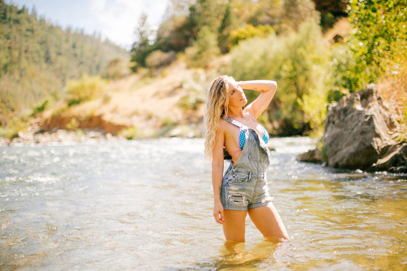 A beautiful blonde woman wearing a blue and pink bikini and overalls standing in the river for an American River boudoir photography session near Auburn, California