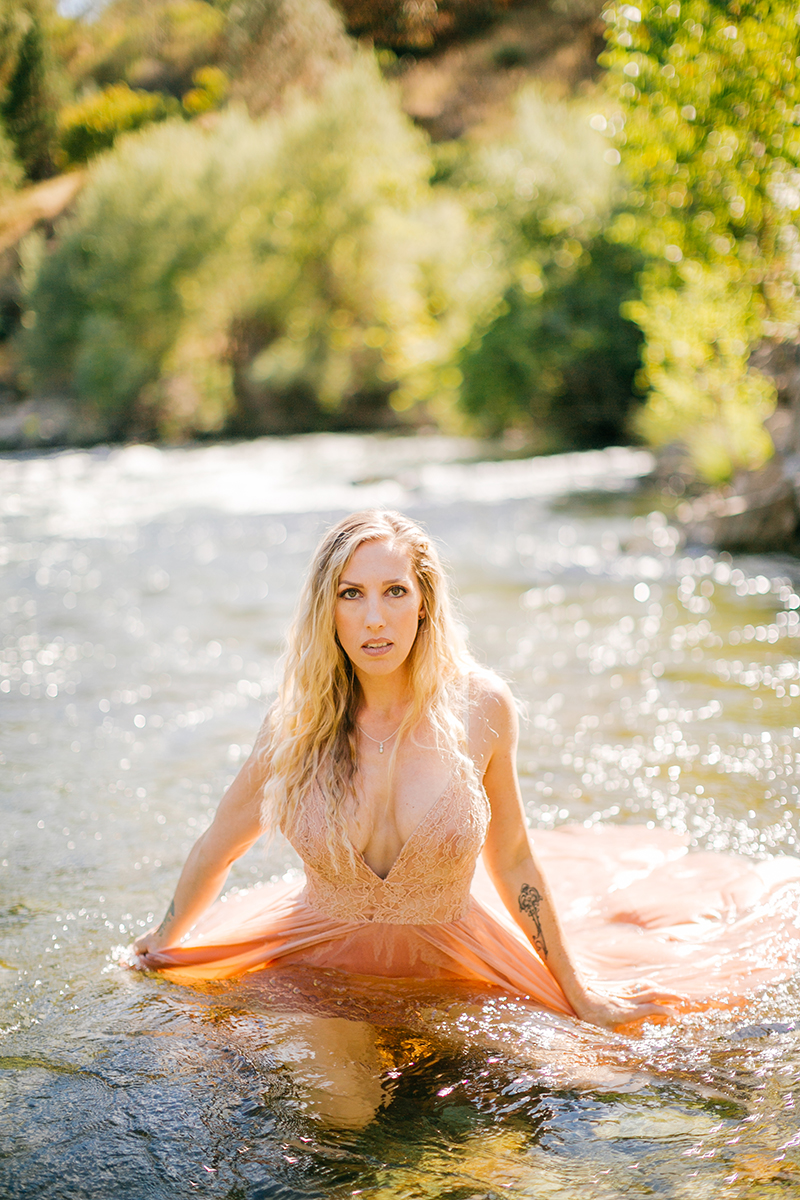 A beautiful blonde woman wearing a pink dress in the water for an American River boudoir photography session near Auburn, California