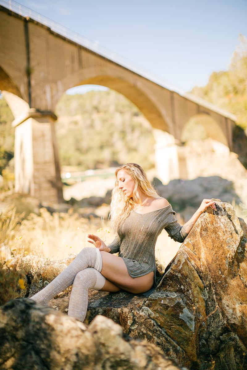 A beautiful blonde woman wearing a green shirt and beige knee high socks sitting on rocks under a bridge for an American River boudoir photography session near Auburn, California