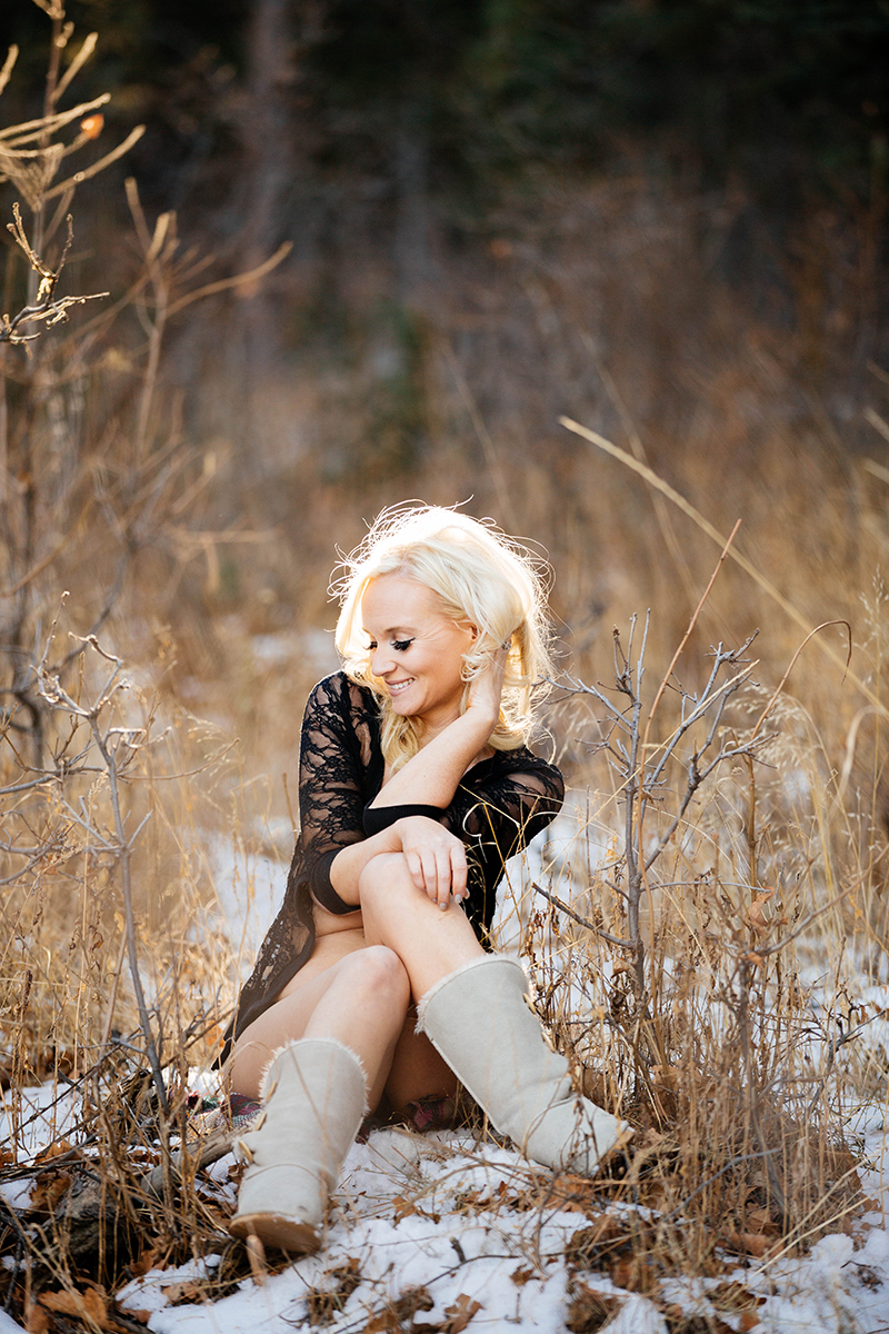 A beautiful blonde woman poses topless for a Blodgett Peak boudoir photography session in Colorado Springs, CO wearing a black lace top and black underwear with tan boots sitting in a field near a forested area as the sun sets