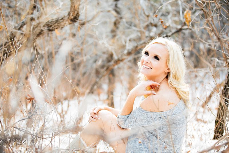 A beautiful blonde woman poses topless for a Blodgett Peak boudoir photography session in Colorado Springs, CO wearing a gray sweater and tan boots sitting in a snow covered field near a forested area as the sun sets