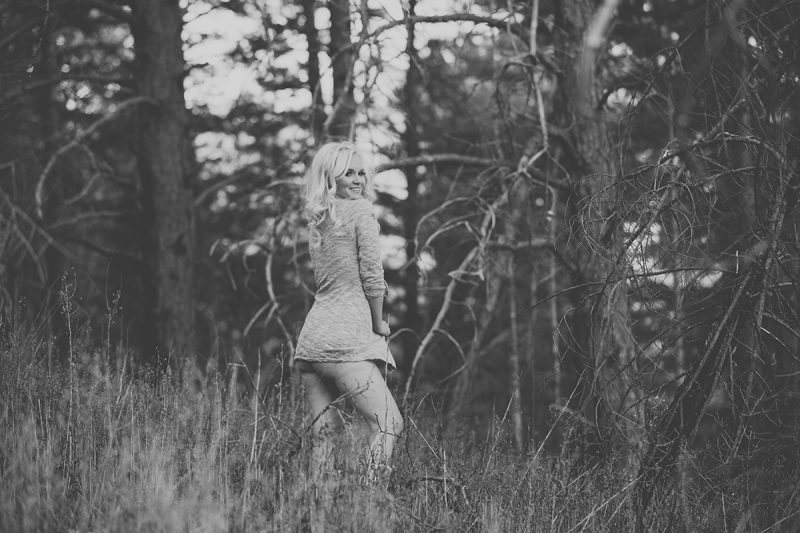 A beautiful blonde woman poses topless for a Blodgett Peak boudoir photography session in Colorado Springs, CO wearing a gray sweater and tan boots standing in a snow covered field near a forested area as the sun sets