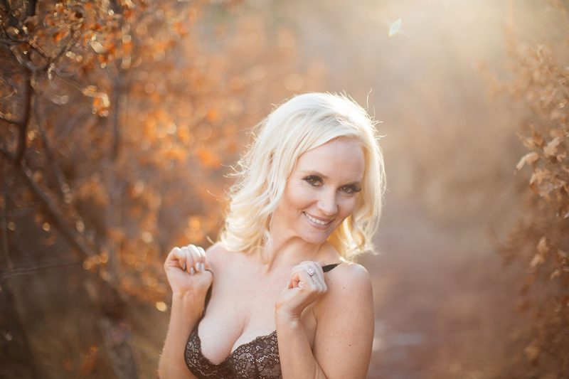 A beautiful blonde woman poses for a Blodgett Peak boudoir photography session in Colorado Springs, CO wearing a black bra on a path with fall colors all around