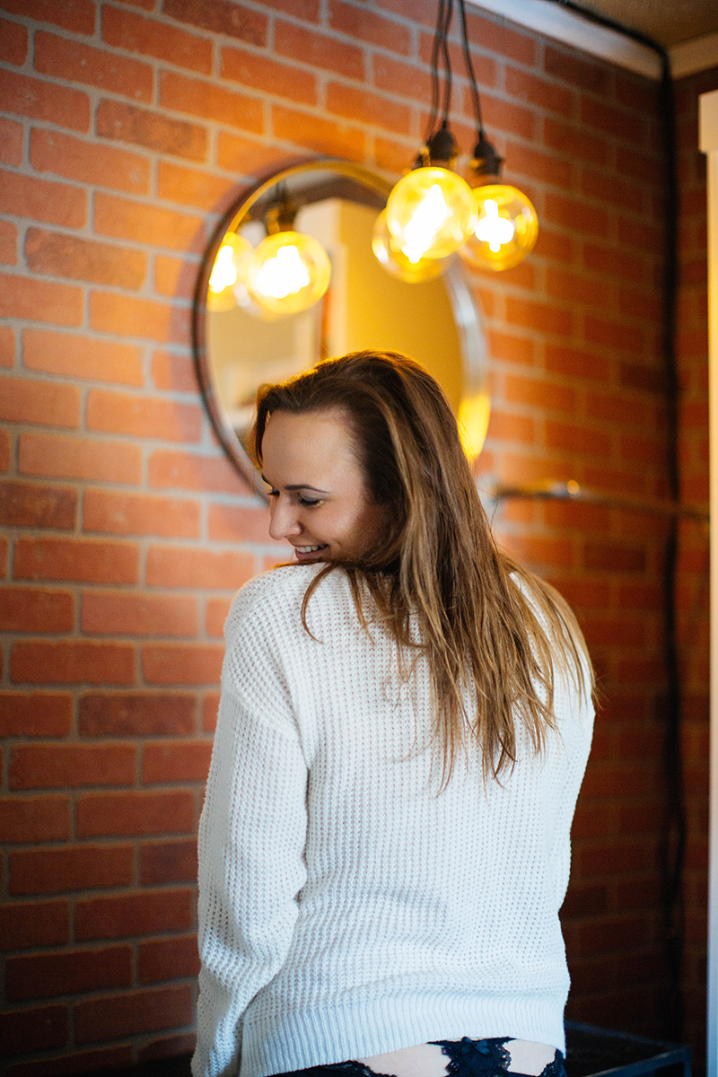 A beautiful woman poses for a Colorado Springs in-home boudoir photography session at her home wearing a white sweater and black underwear in front of a brick wall