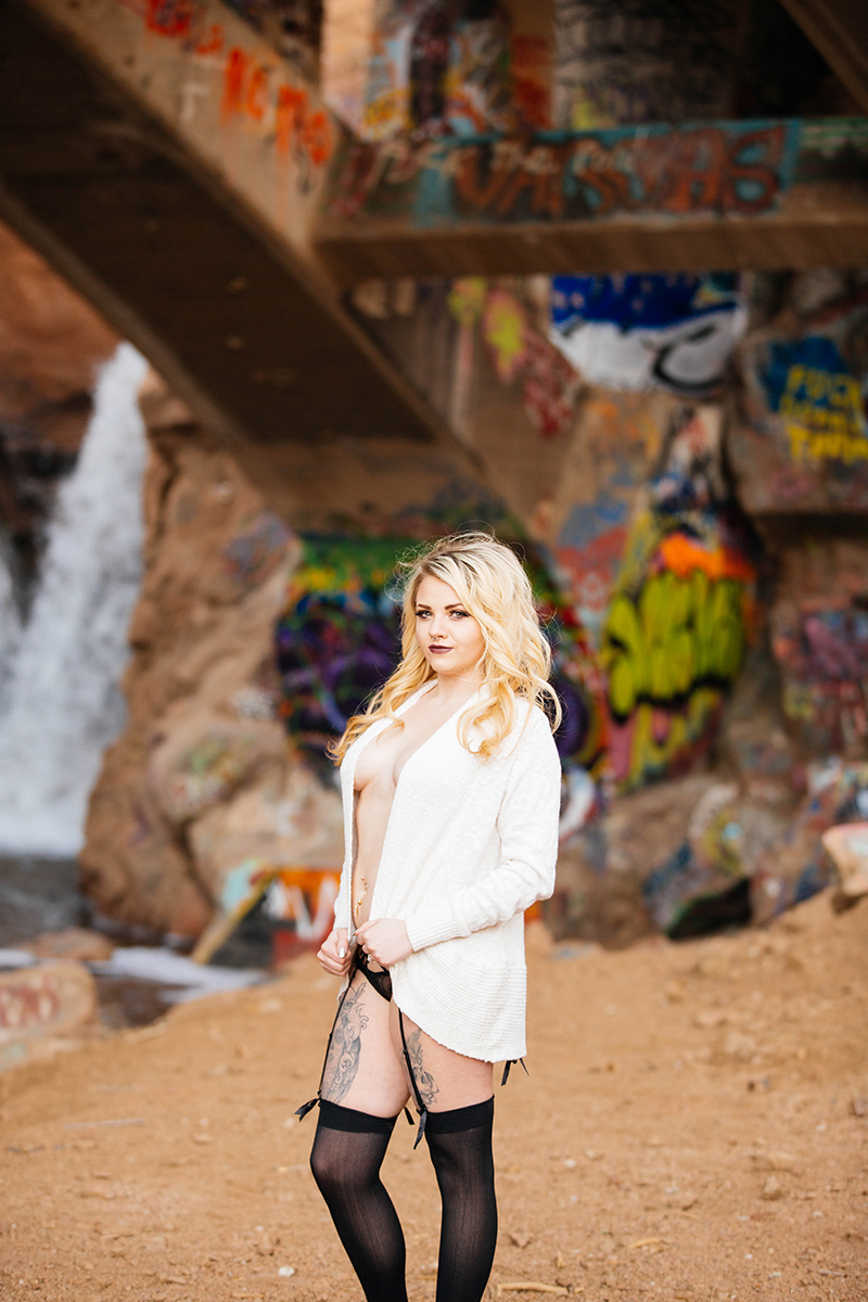 A beautiful young blonde woman poses topless for a Graffiti Falls boudoir photography session in Colorado Springs, CO wearing a white sweater and black underwear in front of a waterfall