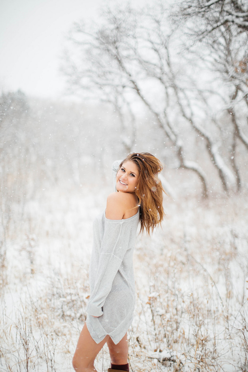 A beautiful young blonde woman poses for a snow boudoir photography session wearing a gray sweater as it snows in a field with trees in Colorado Springs, Colorado.