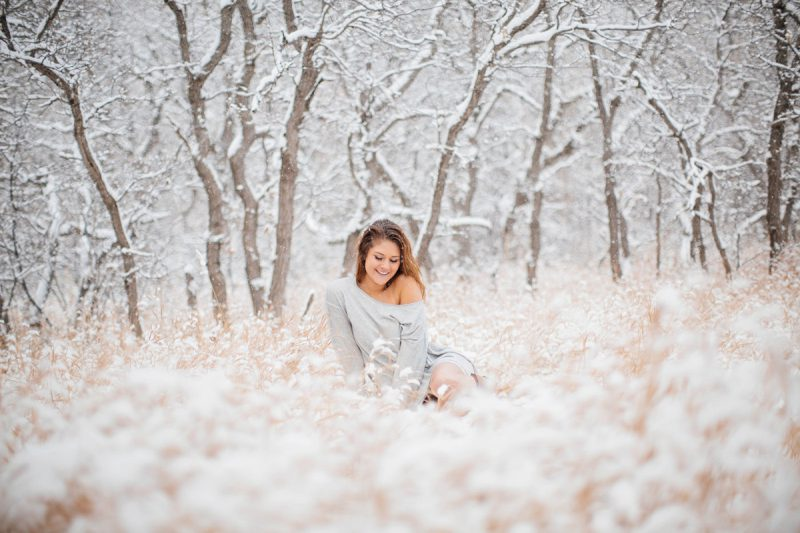 A beautiful young blonde woman sitting for a snow boudoir photography session wearing a gray sweater as it snows in a field with trees in Colorado Springs, Colorado.