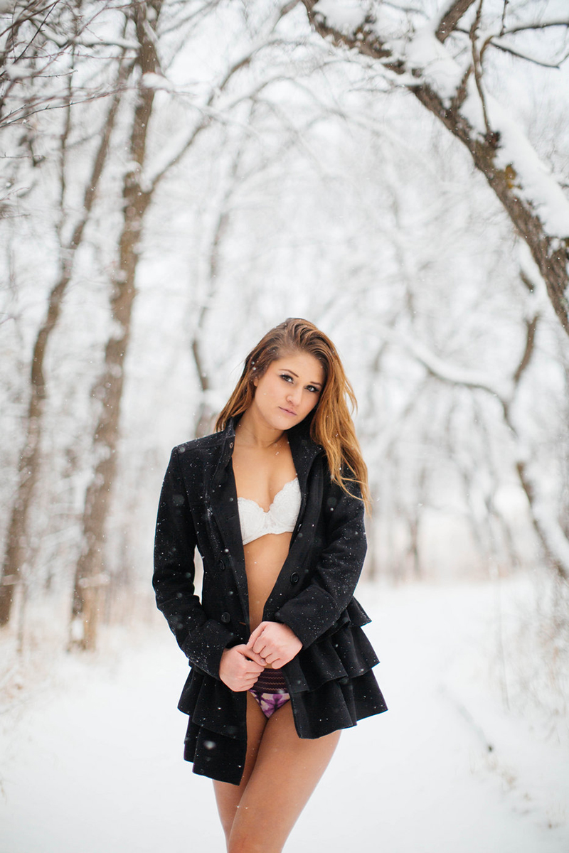 A beautiful young blonde woman poses for a snow boudoir photography session wearing a white bra, black underwear and a black peacoat as it snows on a path with trees all around in Colorado Springs, Colorado.