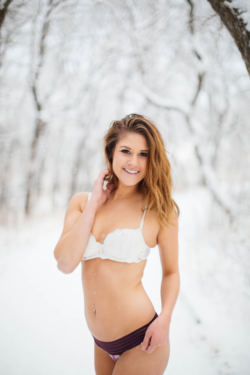 A beautiful young blonde woman poses for a snow boudoir photography session wearing a white bra and black underwear as it snows on a path with trees all around in Colorado Springs, Colorado.