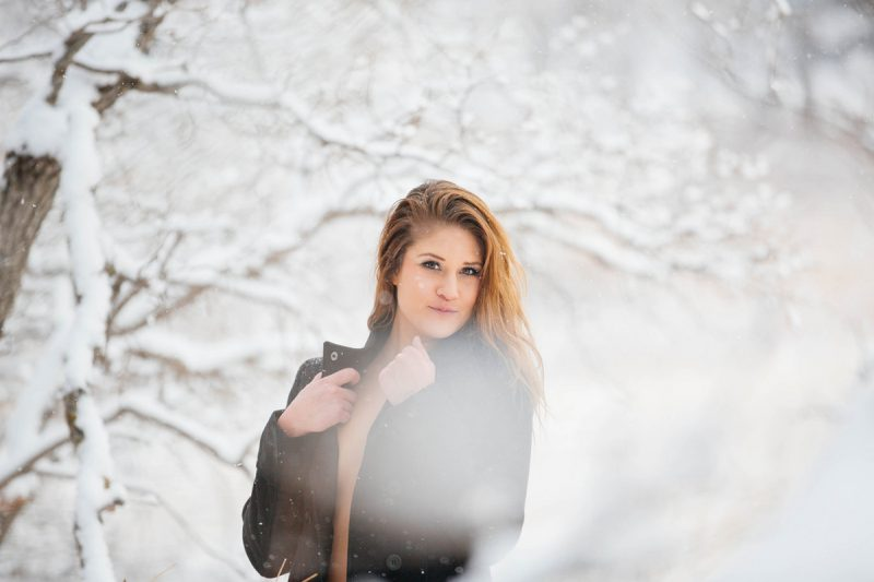 A beautiful young blonde woman poses topless for a snow boudoir photography session wearing black underwear and a peacoat as it snows on a path with trees all around in Colorado Springs, Colorado.