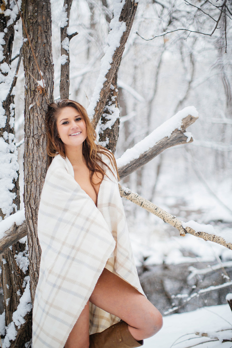 A beautiful young blonde woman poses topless for a snow boudoir photography session wearing purple underwear and a plaid blanket as it snows on a path with trees all around in Colorado Springs, Colorado.