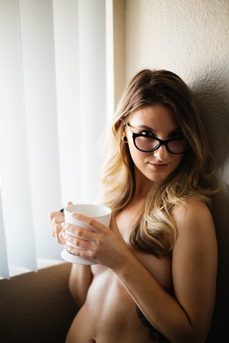 A beautiful young blonde woman poses topless for a Colorado Springs apartment boudoir photography session in her home holding a cup of coffee in her room in front of a window