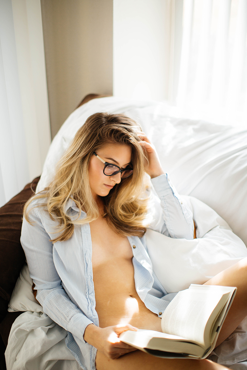 A beautiful young blonde woman poses nude for a Colorado Springs apartment boudoir photography session in her home wearing a light blue button up shirt and reading glasses holding a book on her couch in front of the window