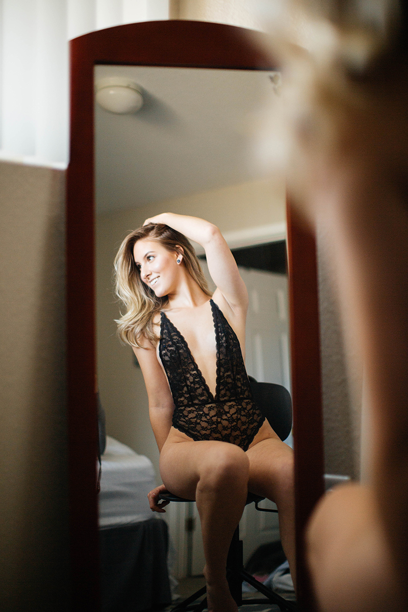 A beautiful young blonde woman poses for a Colorado Springs apartment boudoir photography session in her home wearing black lingerie sitting in front of a mirror