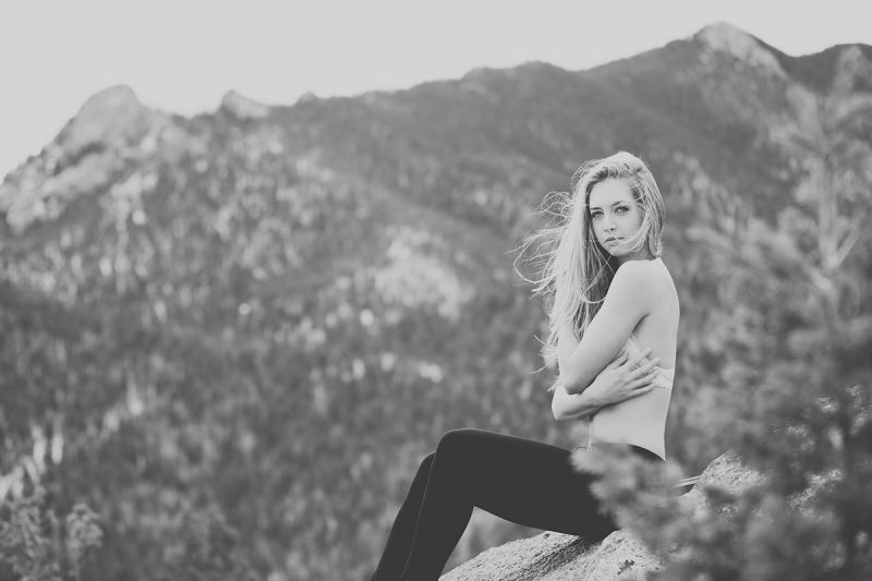 A beautiful young blonde woman poses for a Gold Camp Road boudoir photography session in Colorado Springs, CO wearing a white bralette and black pants sitting on a stone in the Rocky Mountains