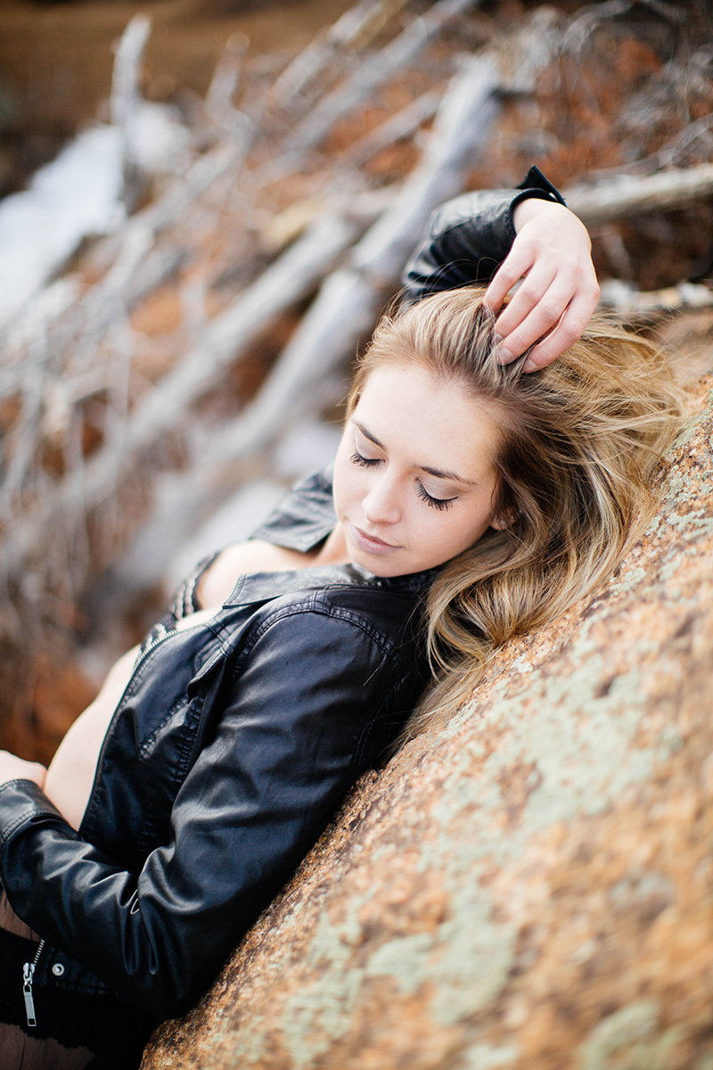 A beautiful young blonde woman poses for a Gold Camp Road boudoir photography session in Colorado Springs, CO wearing a black bra and a black leather jacket in the Rocky Mountains leaning on a boulder