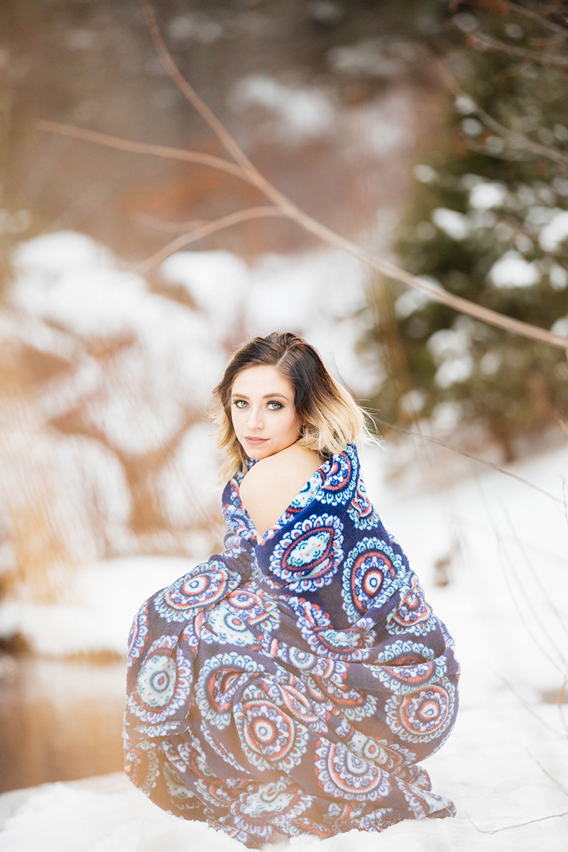 A beautiful young brunette woman poses topless for a Palmer Lake Reservoir boudoir photography session in Colorado Springs, CO wearing a blue blanket kneeling in a snow covered field next to a stream