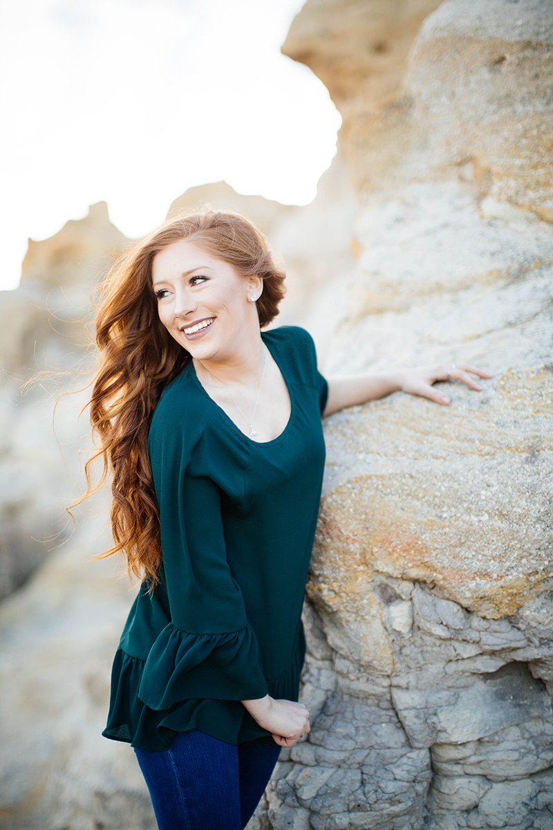 A beautiful young redhead poses for a Palmer Park fashion photography shoot in Colorado Springs, CO wearing a dark green dress leaning against rock formations at sunset