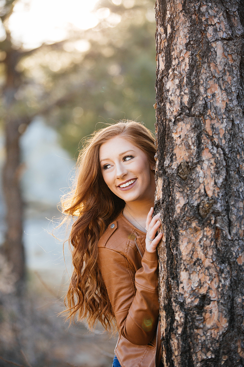 A beautiful young redhead poses for a Palmer Park fashion photography shoot in Colorado Springs, CO wearing a tan leather jacket, a red body suit and jeans while leaning against a tree on the side of a mountain at sunset