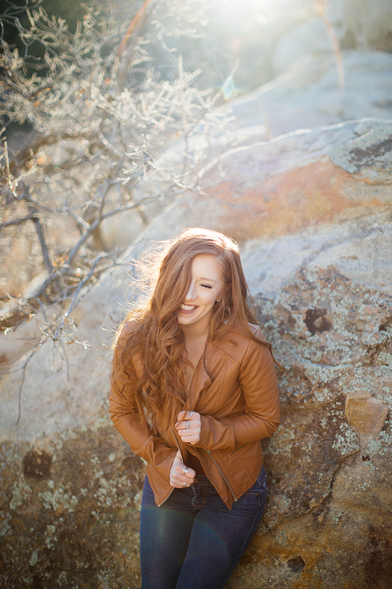 A beautiful young redhead poses for a Palmer Park fashion photography shoot in Colorado Springs, CO wearing a tan leather jacket, a red body suit and jeans while leaning on rock formations on the side of a mountain at sunset